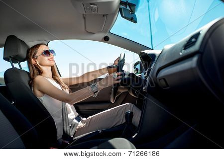 Happy Young Woman With Coffee To Go Driving Her Car