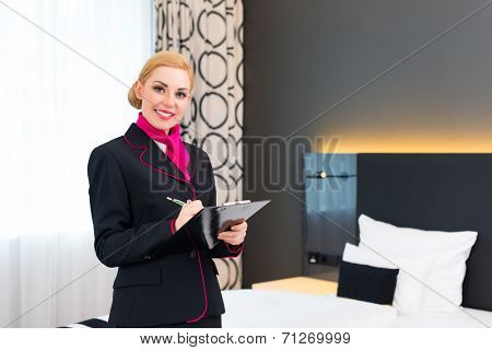 Housekeeping manager or assistant controlling hotel room or suit with checklist on tidiness