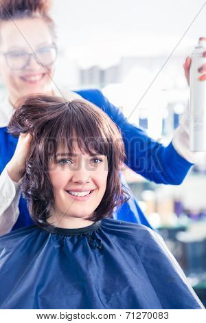 Female coiffeur giving women hairstyling with hairspray in hairdresser shop