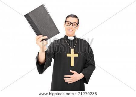 Happy young priest holding a holy bible isolated on white background