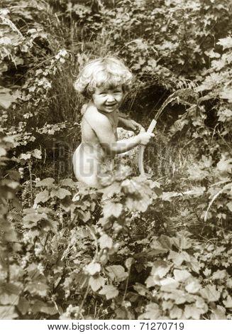 Vintage photo of baby girl watering the garden (early eighties)