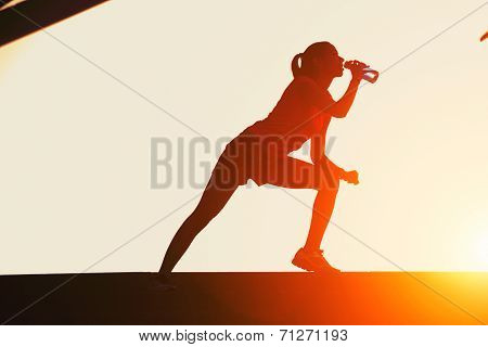 Silhouette of attractive female runner drinking water