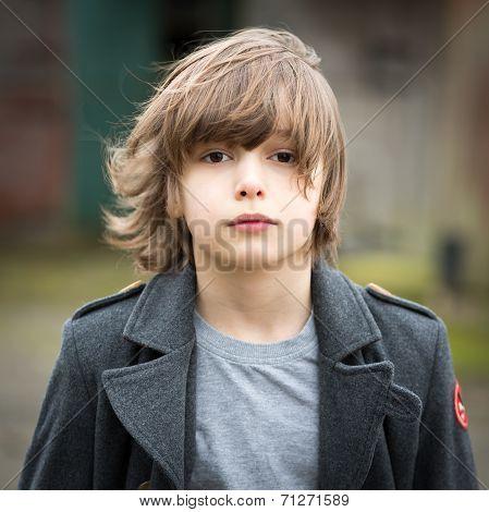 Boy In Long Coat Standing In A Farm Yard