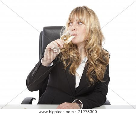Young Woman Sipping Champagne At Her Desk