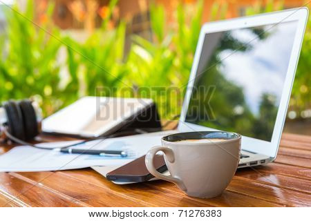 Laptop, tablet , smartphone and coffee cup with financial documents on wooden table