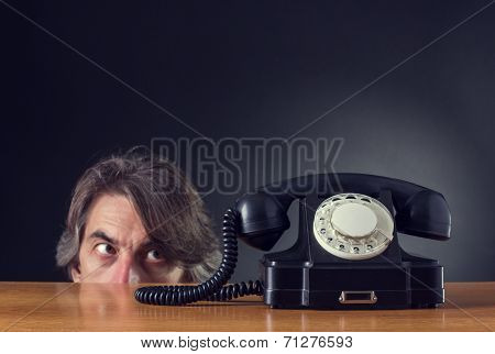Man exasperated looks on retro phoneon