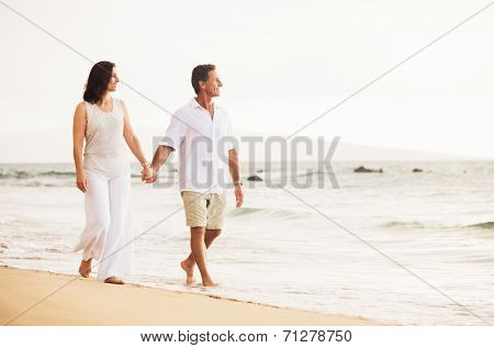 Mature Retired Couple Enjoying Sunset Walk on the Beach