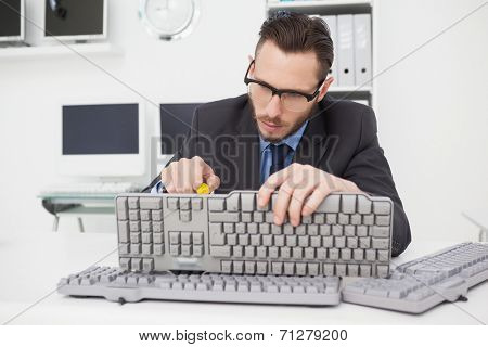 Technician fixing keyboard with screw driver in his office