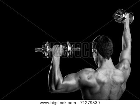 Rear view of a fitness man lifting weights on black background