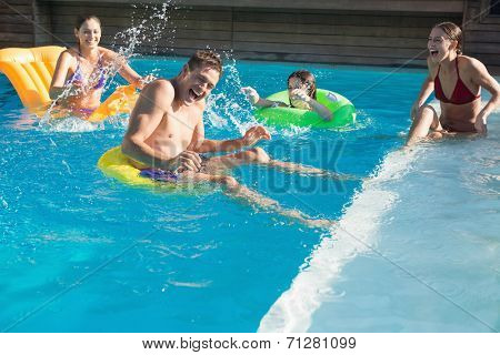 Cheerful young people playing in the swimming pool