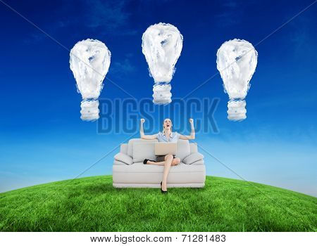 Cheering beautiful businesswoman sitting on couch against cloud light bulbs