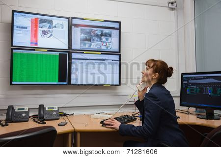 Technician sitting in office running diagnostics in large data center