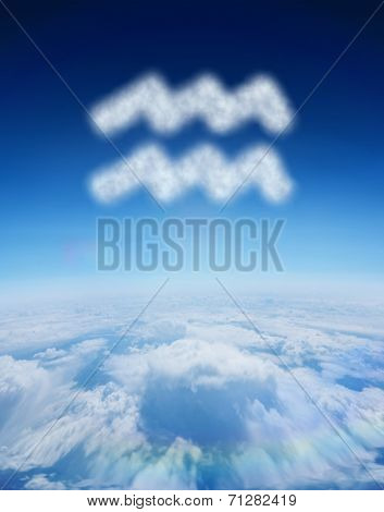 Cloud in shape of aquarius star sign against blue sky over clouds at high altitude