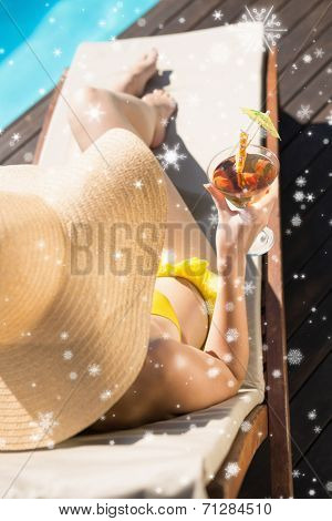 Beautiful woman holding drink by swimming pool against snow falling