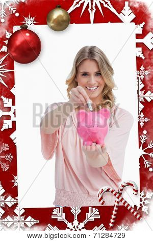 Smiling woman putting money into a piggy bank that she is holding against christmas themed page