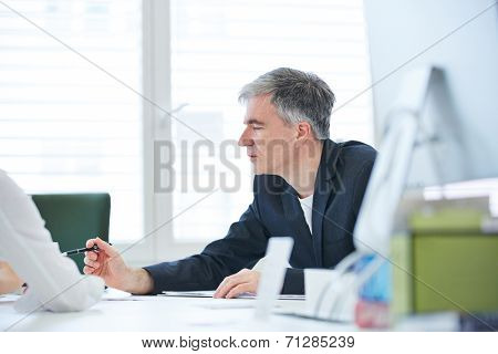 Elderly business man negotiating in meeting in the office