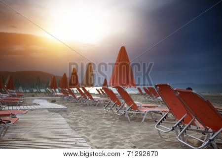 chaise longue on the beach at sunset
