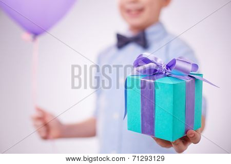 Blue package with lilac ribbon held by a boy