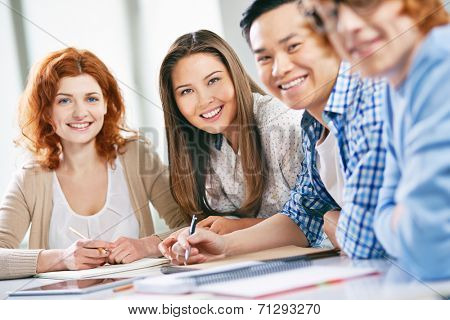 Smart groupmates looking at camera while sitting at lesson