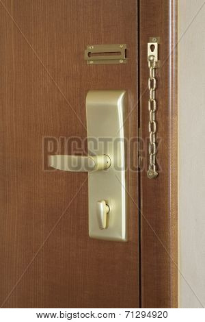 Wooden door with handle and lock of a hotel room