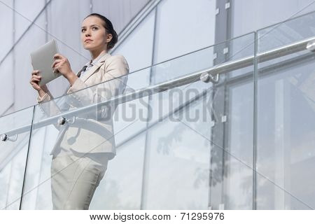 Beautiful young businesswoman holding tablet computer at office railing