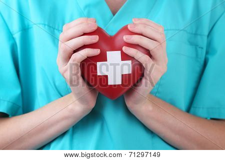 Red heart with cross sign in doctor hand, close-up, isolated on white