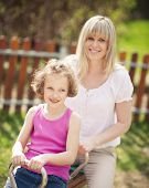 picture of seesaw  - Mother and daughter ride seesaw together - JPG