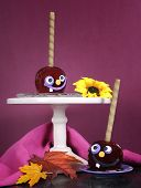 image of toffee  - Happy smiling crazy face red toffee apples candy on stand for trick or treat Halloween food against a bright dark pink red and orange background vertical - JPG