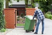 stock photo of dumpster  - Senior man is pushing wheeled dumpster - JPG