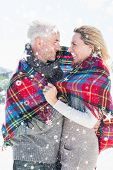 stock photo of blanket snow  - Happy couple wrapped up in blanket standing on the beach against snow falling - JPG