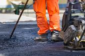 stock photo of work boots  - Construction workers during asphalting road works wearing coveralls - JPG