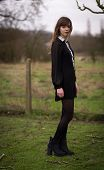 foto of nylons  - Portrait of a beautiful young woman wearing a black dress nylons and boots standing in a country farm field hair blowing in the wind.