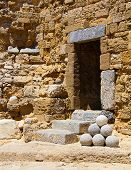stock photo of cannon-ball  - old stone harbor fortress with cannon balls - JPG