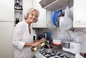 pic of saucepan  - Portrait of senior woman adding olive oil to saucepan at kitchen counter - JPG