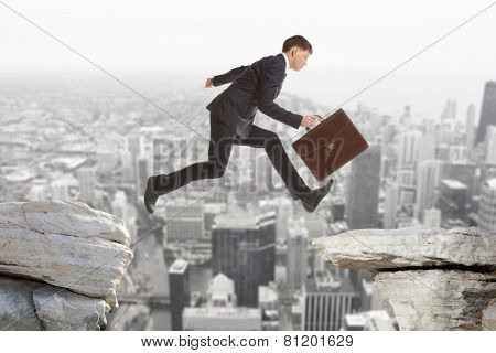 Young businessman jumping over rocks with gap concept