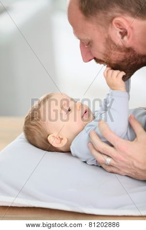 Daddy cuddling baby boy on changing table