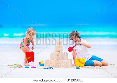 Kids Building Sand Castle On The Beach