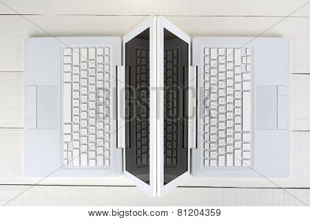 High angle shot of two white laptop computers back-to-back on a white wood table. Horizontal format.