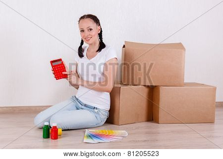 Woman Sits In A Room Near Boxes.