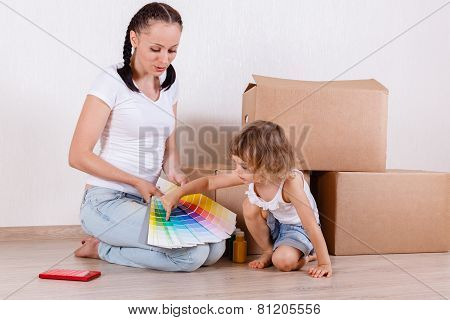 Family Sit In A Room Near The Boxes.