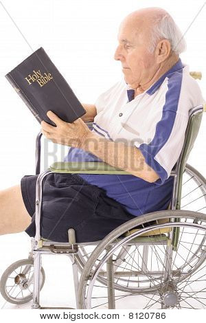 handicap senior in wheelchair reading the bible vertical