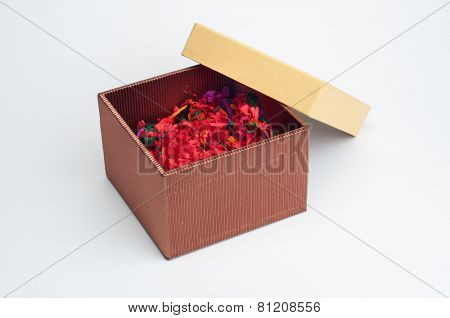 An isolated, half opened gift box filled with decorative colorful shredded paper. Image on white background.