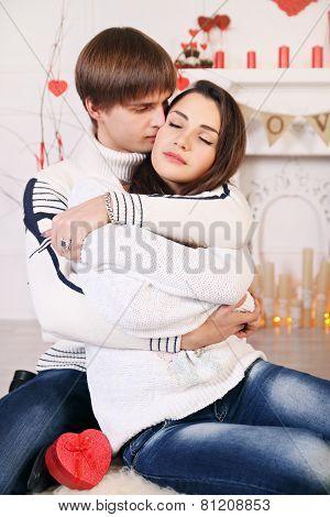Couple Hugging Near A Fireplace