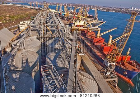 Grain from silos being loaded onto cargo ship on conveyor belt
