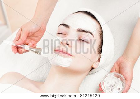 Young woman facial mask applying in beauty parlour