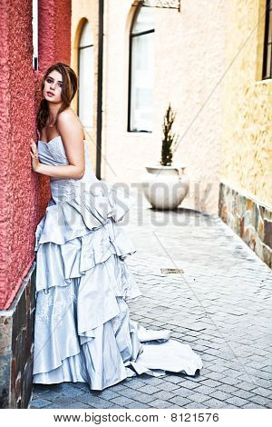 Young Woman In A Gown Leaning Against The Wall
