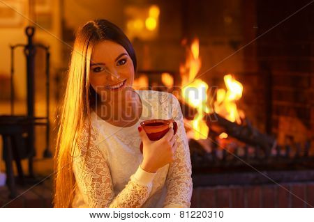 Girl Warming Up At Fireplace Holds Mug