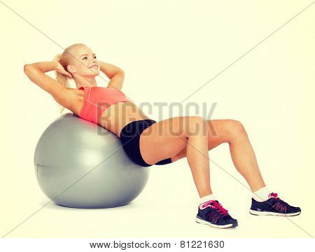 fitness, exercise and diet concept - smiling sporty woman exercising on fitness ball