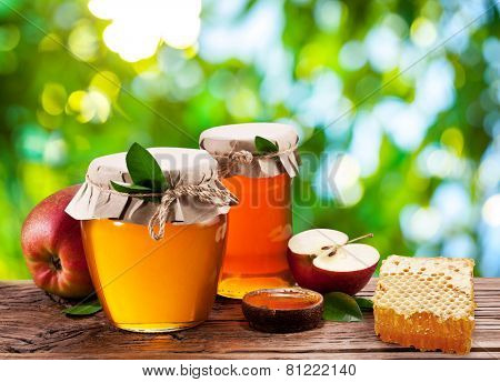Glass cans full of honey, apples and combs on old wooden table in the garden.