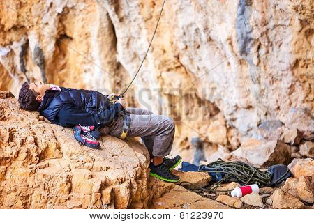 Man watching leading rock climber while belaying